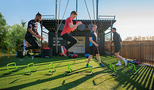 Image of a group of people jumping over small hurdles during a Battlebox class