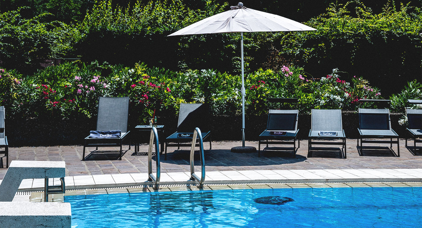Outdoor swimming pool with sun loungers at David Lloyd Malaspina