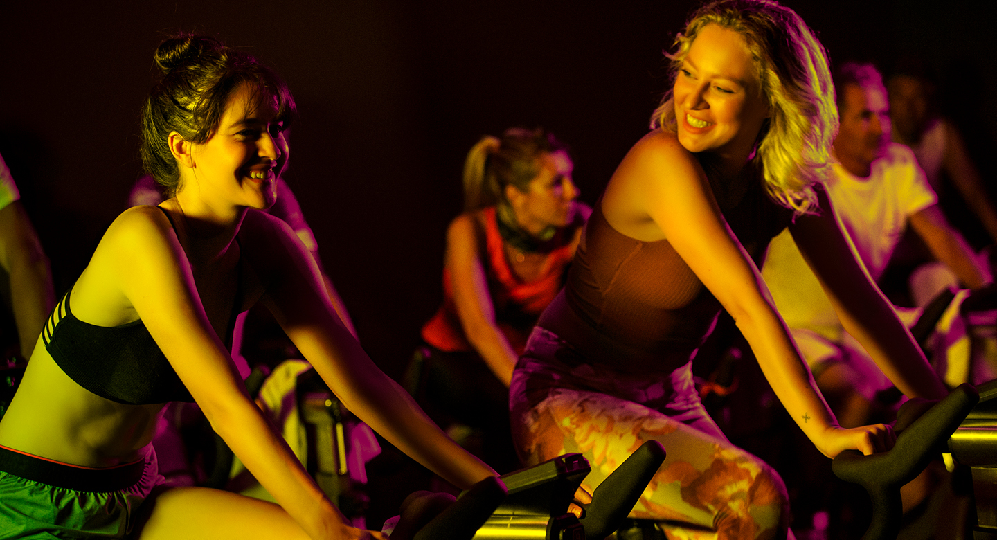 Two women smiling  and talking while taking part in a spin class