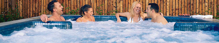 4 people laughing together in an outdoor jacuzzi.