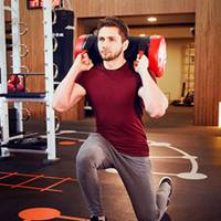 Man lunging with weighted bag in the gym